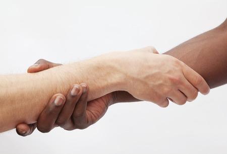 young men: Two young men shaking hands, close-up, studio shot