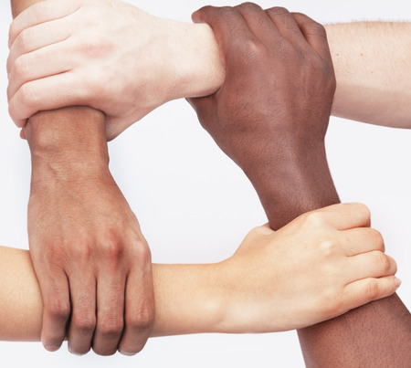 Four young people holding each others wrists in a circle, close-up, studio shot photo