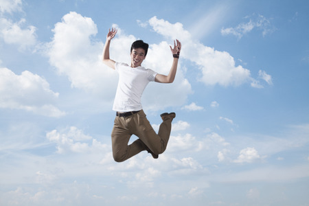 above 21: Young smiling man jumping in mid-air, sky and cloud background Stock Photo