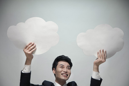 two visions: Smiling businessman holding two paper clouds, studio shot