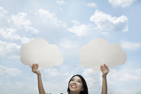 above 25: Young woman holding two cut out paper clouds against a blue sky with clouds Stock Photo