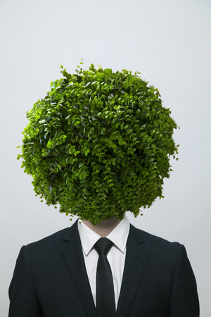obscuring: Businessman with a circular bush obscuring his face, studio shot Stock Photo