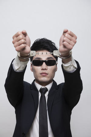 Cool businessman with sunglasses in handcuffs, studio shot Stock Photo