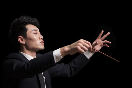 arms above head: Young conductor with baton raised, black background Stock Photo