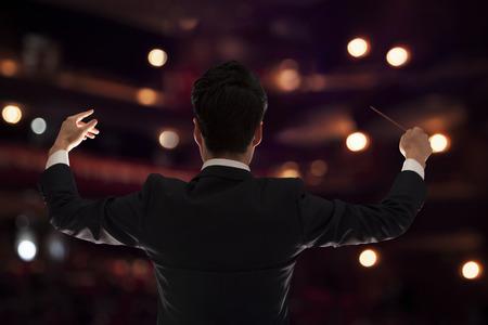 Junge Dirigent mit Taktstock zu einem Performance erhöht, Rückansicht
