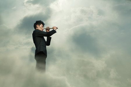 Young businessman looking through telescope in a dreamlike cloud photo