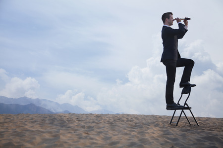 Businessman standing on a chair and looking through a telescope in the middle of the desert  photo