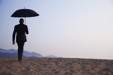 Businessman holding an umbrella and walking away in the middle of the desert photo