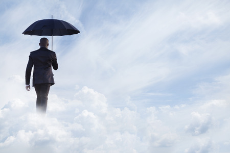 above 25: Businessman holding an umbrella and walking  away in dreamlike clouds Stock Photo