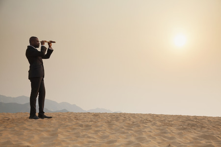 desert scenes: Young businessman looking through telescope in  the middle of the desert