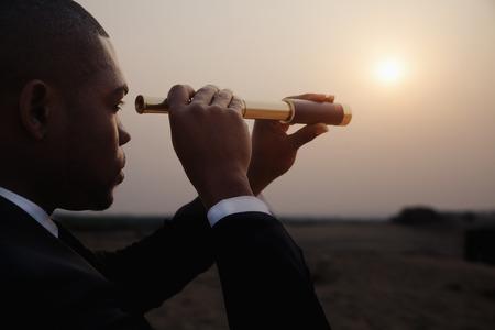Junger Geschäftsmann sucht mit dem Fernrohr in der Mitte der Wüste Lizenzfreie Bilder