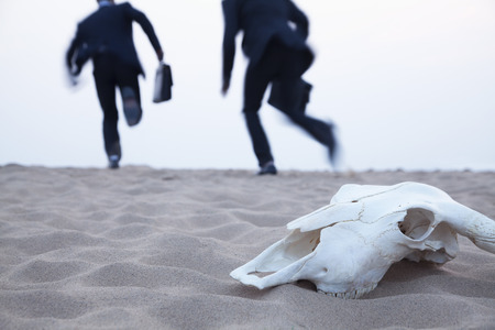 Two businessmen running away from an animal skull in the middle of the desert