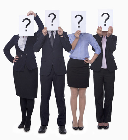 anonymity: Four business people holding up paper with question mark, obscured face, studio shot Stock Photo