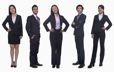 Portrait of five young smiling businesswomen and young businessmen, looking at camera, studio shot photo
