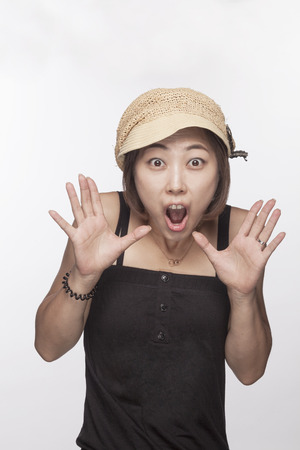 Portrait of surprised woman with hands raised, studio shot Imagens