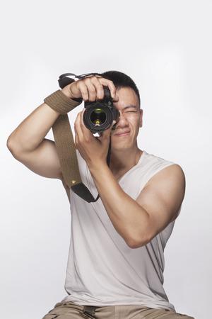 slur: Man holding a camera and taking a photograph, studio shot