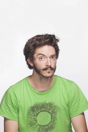 raised eyebrows: Young man with eyebrow raised looking at camera, studio shot Stock Photo
