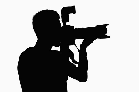 Silhouette of man holding camera.