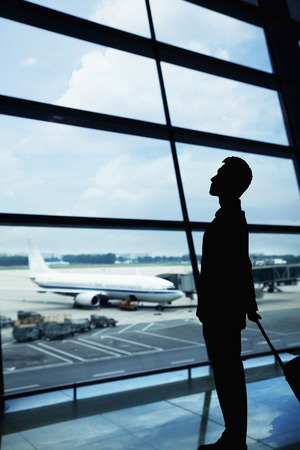 above 25: Silhouette of businessman waiting in the airport and looking out the window