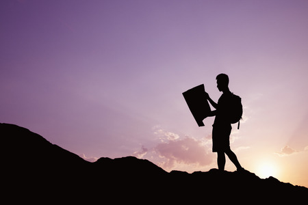 Silhouette of young man looking at a map in nature while hiking photo