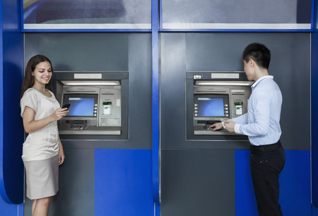withdrawing: Two people standing and withdrawing money from an ATM