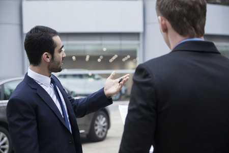 Car salesman holding car keys and selling a car to a young businessman Imagens