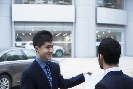 자동차 세일즈맨 자동차 키와 서류를 들고 젊은 사업가에 차를 판매
