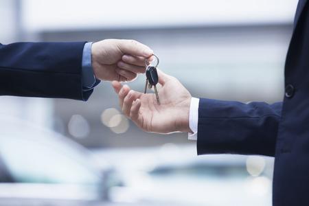 Vendedor de coche que la entrega de llaves de un coche nuevo a un joven hombre de negocios, primer plano