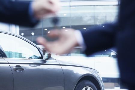 車のセールスマンが青年実業家に新しい車のキーを引き渡すクローズ アップ