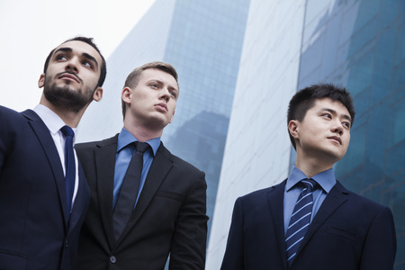 three day beard: Portrait of three serious businessmen, outdoors, business district