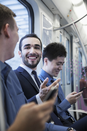 Three businessmen sitting in a row and talking on the subway photo