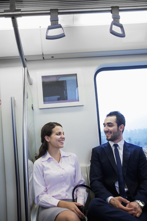 above 21: Two young business people sitting and chatting on the subway Stock Photo