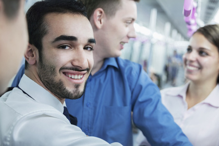 Portrait of young smiling businessman standing on the subway, looking at camera  photo
