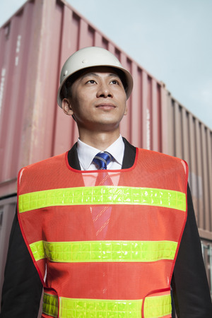 protective workwear: Proud engineer in protective workwear standing in a shipping yard