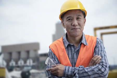 protective workwear: Portrait of proud worker with arms crossed in protective workwear outside of a factory