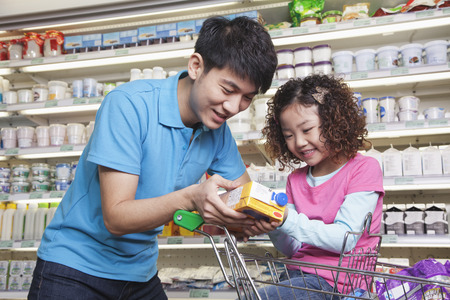 25 29 years: Father and Daughter Shopping in Supermarket, Looking at Juice Box