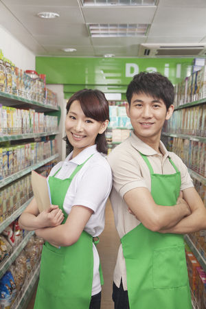 30 34 years: Two Sales Clerks Standing in a Supermarket LANG_EVOIMAGES