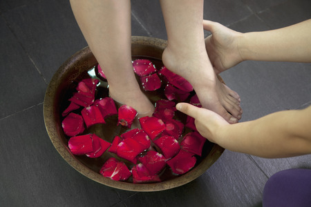 55 59 years: Woman s Feet Soaking in Water with Rose Petals LANG_EVOIMAGES