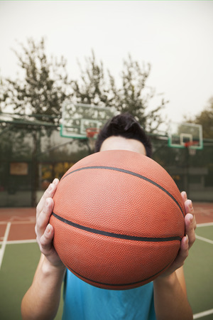 Young man covering his face with basketball, portrait