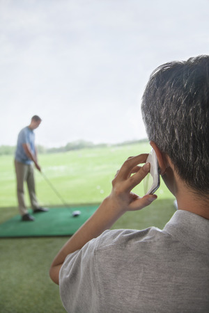 Rear view of man on the phone while another man plays golf in the background Stock Photo