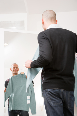coathangers: Man holding a sweater