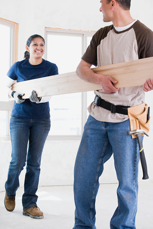 A couple holding a plank of wood photo