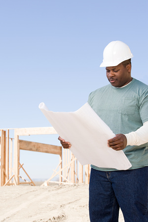 A builder holding a blueprint Stock Photo