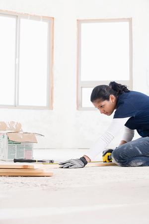A female builder measuring a plank of wood Foto de archivo