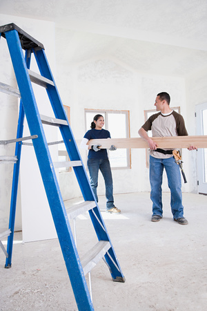 tradespeople: A couple holding a plank of wood