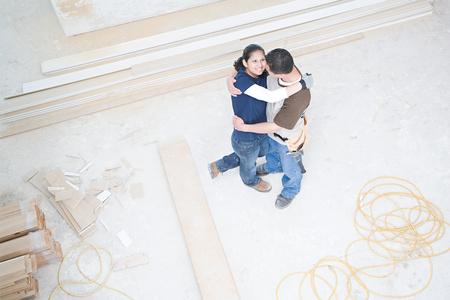 Couple hugging in their new home photo