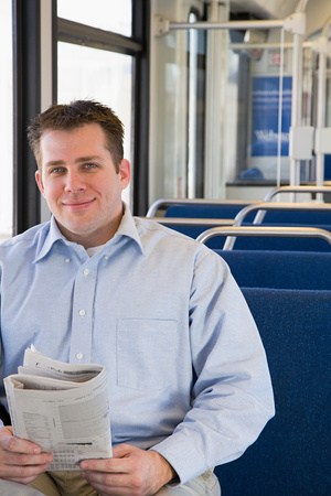 Man on train with newspaper Stock Photo