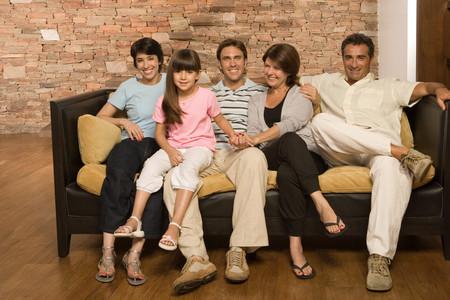 ni�os latinos: Familia en un sof� Foto de archivo