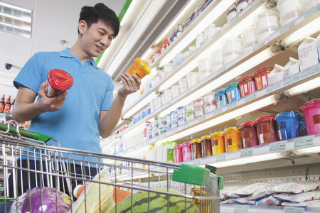 three shelves: Young Man Making Decisions About Food in Supermarket