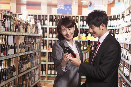Couple Choosing Wine in a Liquor Store photo